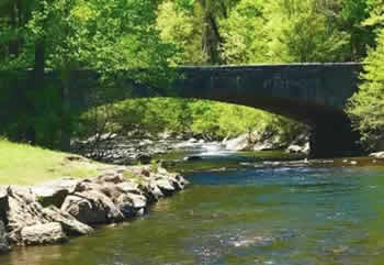 Stone bridge over a stream with rushing waters in the Great Smoky Mountains National Park